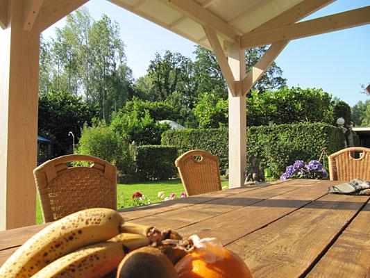 TantraTempel veranda met groepstafel in de prachtige tuin met heel veel bloemen