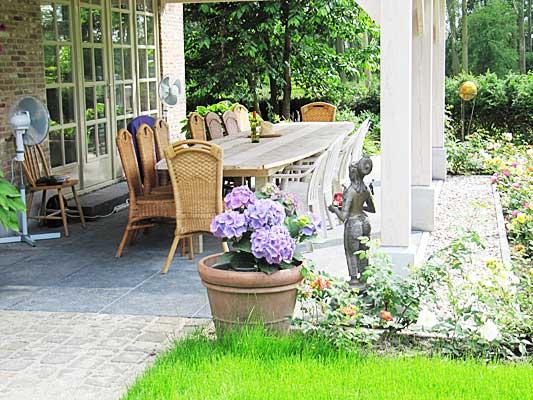TantraTempel veranda met grote groepstafel en veel bloembakken