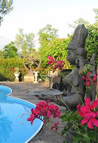 TantraTempel Deepam Lakshmi Godinnen die het Licht brengen bij de jacuzzi aan het heerlijke zwembad met heel veel mooie bloemen in de zomer